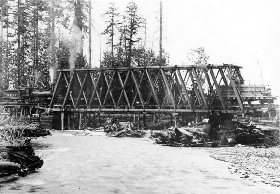 Engine 217 shown pulling a load of empty flatcars with one loaded at right on Sequim's historic railroad bridge.